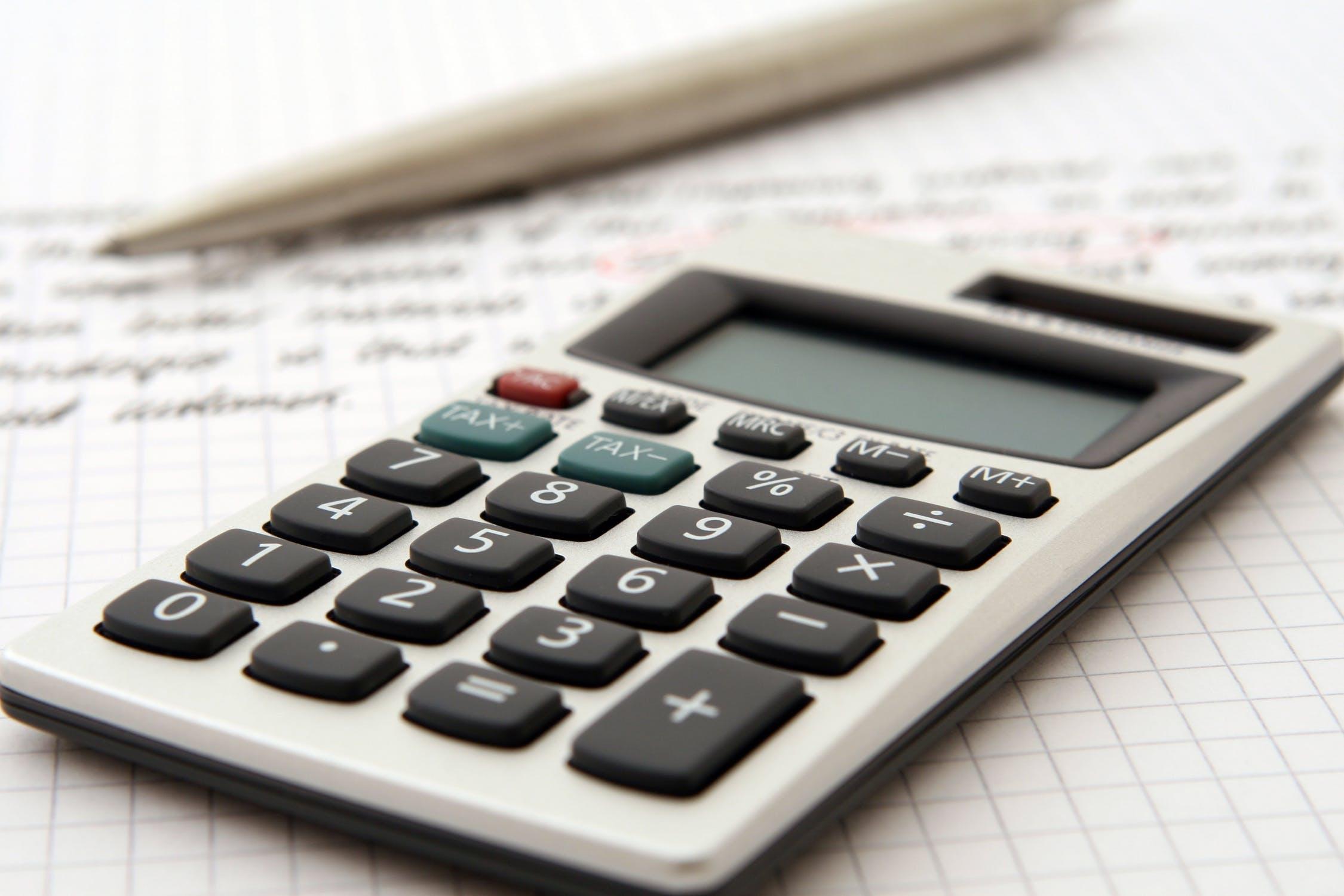 Kalkulator naukowy na tle zapisanej kartki w kratkę