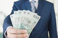 Osoba w garniturze trzymająca rozłożone banknoty o nominale sto złotych