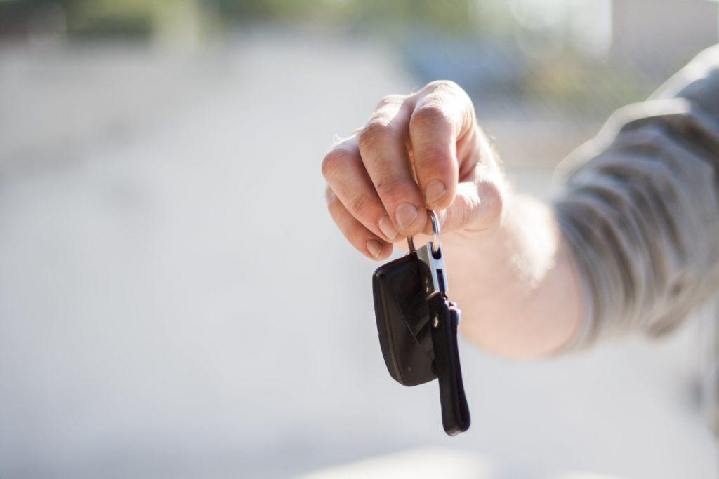 Mężczyzna trzymający kluczki do auta na tle drogi