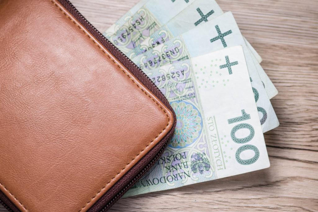 Zbliżenie na banknoty stu złotowe na tle brązowego portfela