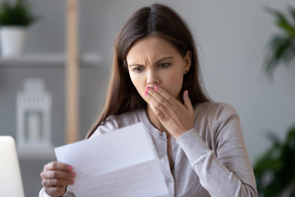 Zszokowana zestresowana młoda kobieta czytająca list z banku o problemie zadłużenia finansowego