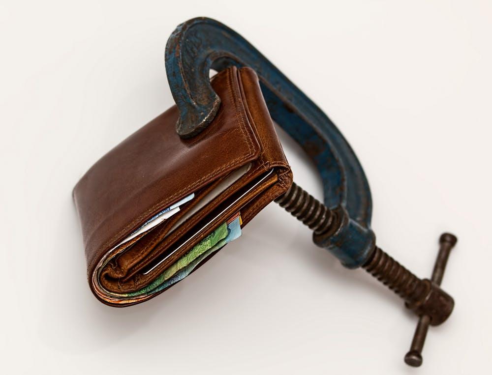 Zaciśnięty, wypełniony banknotami portfel
