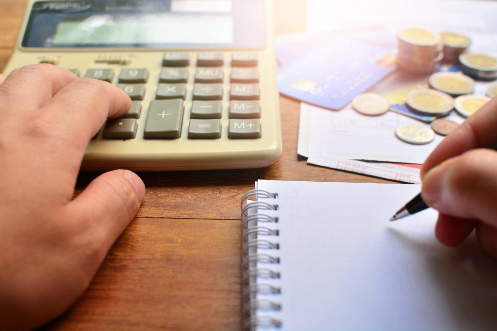 ręka na tle kalkulatora i zeszytu, obliczająca koszt pożyczki i długów