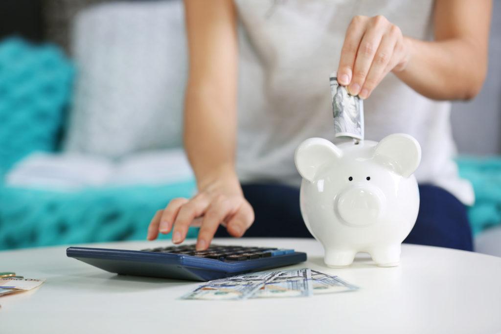 Kobieta licząca na kalkulatorze i wkładająca banknoty do świnki skarbonki