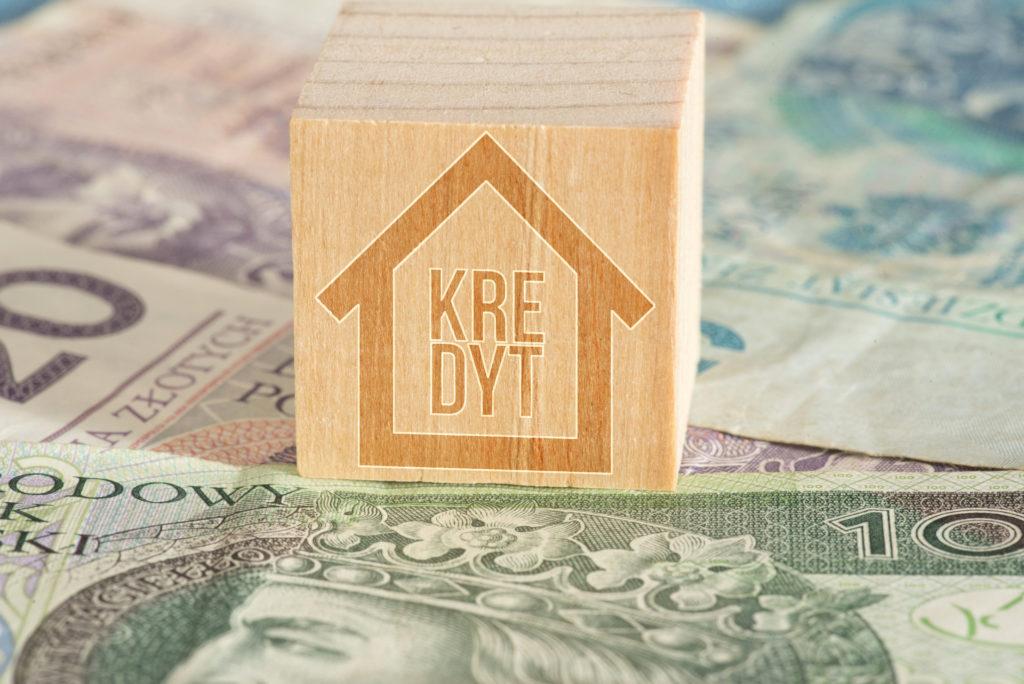 Polskie banknoty PLN i drewniana kostka kredyt