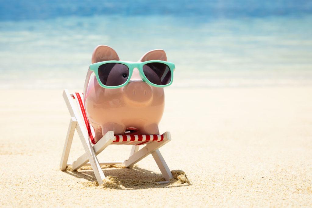 Świnka skarbonka w turkusowych okularach na miniaturowym leżaku na plaży